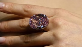 A model poses with a 59.60-carat oval mixed-cut pink diamond, known as 'The Pink Star'