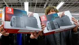 Customers pose with their Nintendo Switch game consoles