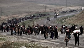 Iraqi families walk down a road as they flee Mosul