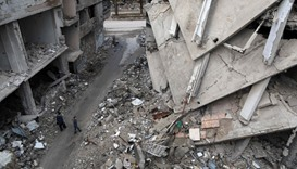 Syrian boys walk amidst destroyed buildings in the Syrian rebel-held town of Arbin