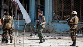 Afghan officials investigate the site of a suicide bomb attack near a Shia mosque in Kabul