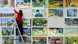 Joanna Maleszyk hanging up reproductions of Vincent van Gogh paintings at a film studio in the north