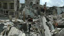 A Syrian boy carries food as he walks amid the rubble of buildings which were destroyed earlier in a