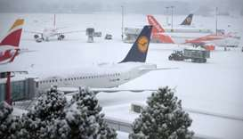 A tractor removes snow next to EasyJet and Lufthansa aircrafts during a temporary closure at Cointri