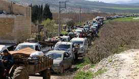 Syrian civilians ride their cars through Ain Dara in Syria's northern Afrin region as they flee Afri