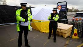 British police officers stand on duty at a cordon near a parking meter covered in a protective tent