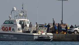 Hellenic Coast Guard officers and locals transfer the bodies of migrants that were drowned when the