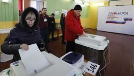 Voters cast their ballots at a polling station during the presidential election in Moscow