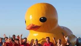 Swimmers posing with a giant inflatable duck they named Daphne in Perth.