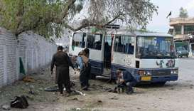 Afghan security personnel inspect the site of bomb blast in Jalalabad