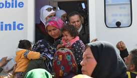 Civilians, fleeing the city of Afrin in northern Syria, gather around a World Health Organization (W