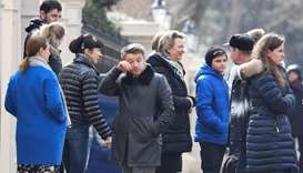 Embassy staff react as colleagues and children board buses outside Russia's Embassy in London, Brita