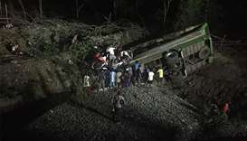 people and rescuers searching for survivors after a passenger bus plunged off a cliff in Sablayan to