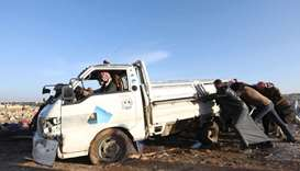 Displaced Syrians push a damaged vehicle following a reported air strike on a refugee camp near the