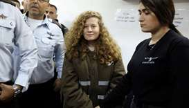 Ahed Tamimi enters a military courtroom escorted by Israeli security personnel at Ofer Prison