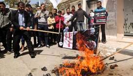 Palestinians burn a dummy representing Palestinian president Mahmud Abbas during a protest in Gaza C