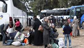 Syrian civilians and rebel fighters arrive in the village of Qalaat al-Madiq, north of Hama