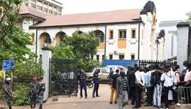 Police officers and people stand outside the high court in Freetown