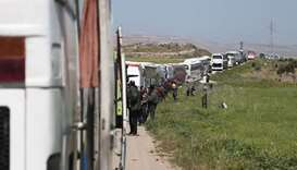 A convoy transporting Syrian civilians and rebel fighters evacuated from Eastern Ghouta waits in a g