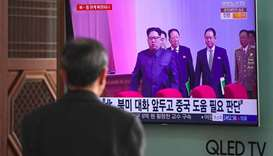 A man watches a television news report about a suspected visit to China by North Korean leader Kim J