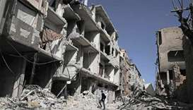 A Syrian man walks down a street past destoyed buildings in Douma, in Eastern Ghouta
