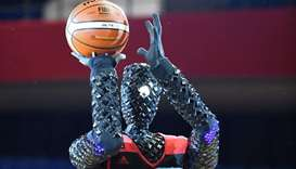 The basketball-playing robot named CUE prepares to shoot the ball during a show rehearsal