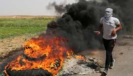 A Palestinian runs next to burning tyres during clashes along the Israel border with Gaza ahead of a