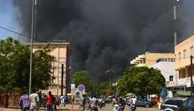 People watch as black smoke rises as the capital of Burkina Faso came under multiple attacks yesterd