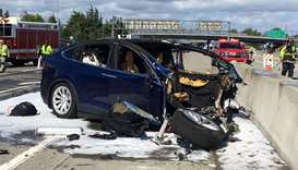 Rescue workers attend the scene where a Tesla electric SUV crashed into a barrier on US Highway 101