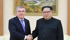 North Korean leader Kim Jong-Un (R) shaking hands with President of the International Olympic Commit