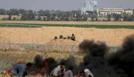 Palestinians take cover from Israeli snipers during clashes at the Gaza-Israel border at a protest
