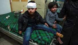 A bandaged Syrian child sits on a bed next to another child after receiving medical attention at a m