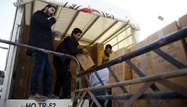 Workers unload parcels of humanitarian aid at the besieged town of Douma, Eastern Ghouta, Damascus,