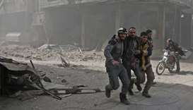 Volunteers from the Syrian civil defence help a man in Hamouria during Syrian government shelling on