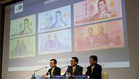 Central bank governor Veerathai Santiprabhob unveils new baht bank notes featuring Thailand's King M