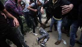 Palestinians help evacuate an injured protester during clashes with Israeli troops near Khan Yunis b