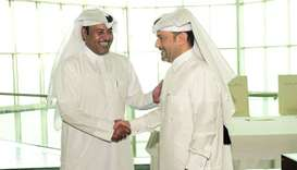 Ahmad al-Namla and Hamad Jumaa al-Mannai shake hands after signing the agreement.