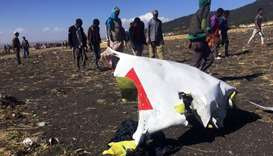 People walk past a part of the wreckage at the scene of the Ethiopian Airlines Flight ET 302 plane c