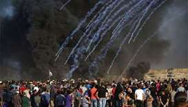 Palestinian protesters watch as tear gas canisters fired by Israeli forces land through black smoke