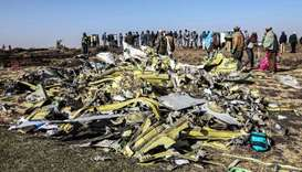 People stand near collected debris at the crash site of Ethiopia Airlines near Bishoftu