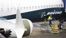 A worker is pictured next to a Boeing 737 MAX 9 airplane on the tarmac at the Boeing Renton Factory