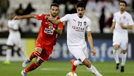 Al Sadd's Baghdad Bounedjah (R) drives the ball