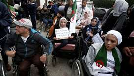 People with special needs, accompanied by their families, take part in a protest demanding immediate