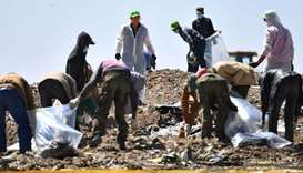 People work to search for belongings and debris for forensic analysis at the crash site of the Ethio