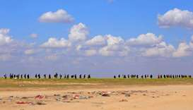 Civilians walk together near Baghouz, Deir Al Zor province, Syria