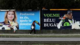 A woman walks past election posters in Bratislava