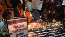 Pakistani demonstrators hold placard and candles during a candlelit vigil the day after the deadly a