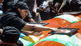 A mourner of victims of the crashed accident of Ethiopian Airlines touches a portrait on a coffin du
