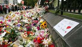 Residents look at flowers in tribute to victims in Christchurch