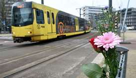 Flowers have been set up in tribute to victims at the site of a shooting in a tram, at 24 October sq